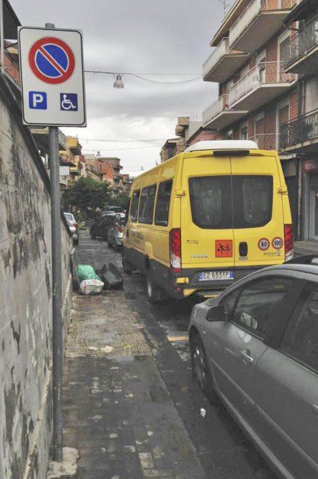 Lo scuolabus del Comune di Biancavilla sui posti auto riservati ai disabili